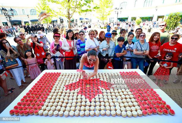 A crowd gathers to watch as Cera Rivers applies icing to the last of 512 cupcakes that make up a Canadian flag during a celebration of Canada's 150th...