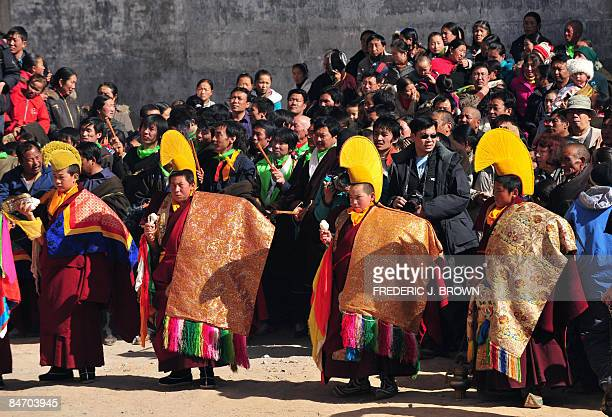 A crowd gathers to watch as Tibetan Buddhist monks take part in activities leading up to the Sunning of the Buddha when a huge silk thangka showing...