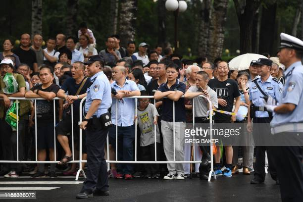 A crowd gathers to watch at the gate of the Babaoshan cemetery during the funeral of former Chinese premier Li Peng in beijing on July 29 2019 The...