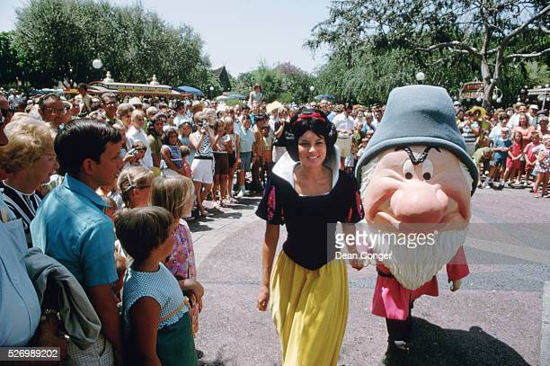 A crowd gathers to watch Snow White and Grumpy on a sunny day at Disneyland Anaheim California 1969