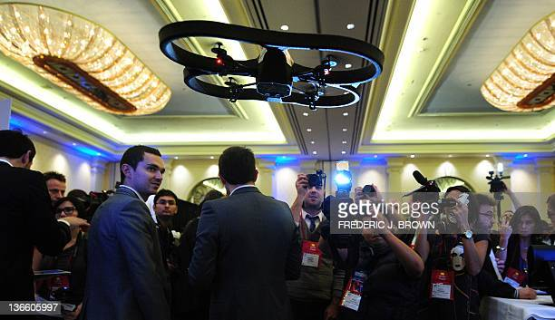 A crowd gathers to watch the Parrot 'ARDrone 20' flying in mid air during a demonstration at CES Unveiled ahead of the opening of the annual Consumer...