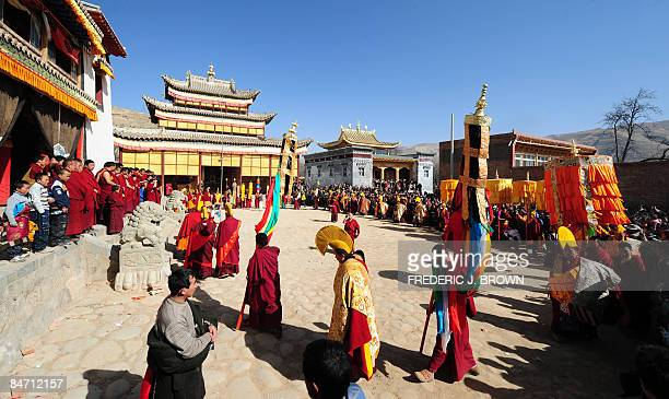 A crowd gathers to watch Tibetan Buddhist monks in a ceremony leading up to the Sunning of the Buddha when a huge thangka of Sakyamuni the founder of...