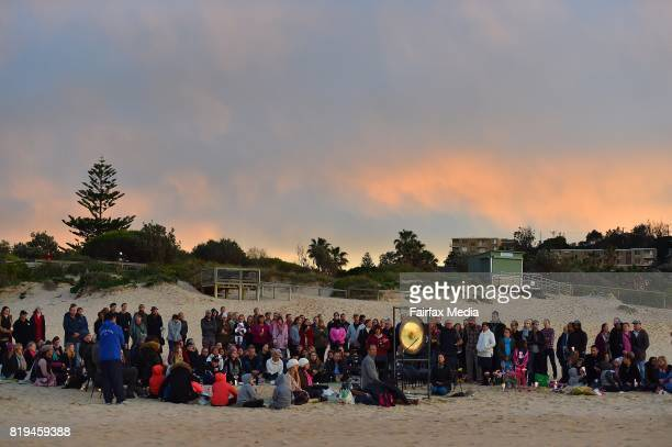 A crowd gathers with John Ruszczyk and Maryan Heffernan the parents of Justine Damond during a vigil for their daughter at Freshwater Beach on July...