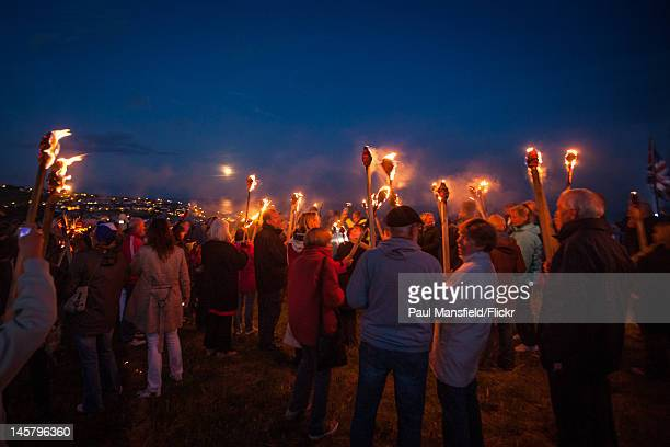 A crowd gathers with lighted torches for the lighting of the Beacon at Rottingdean June 4 2012 to celebrate the Diamond Jubilee of Queen Elizabeth II