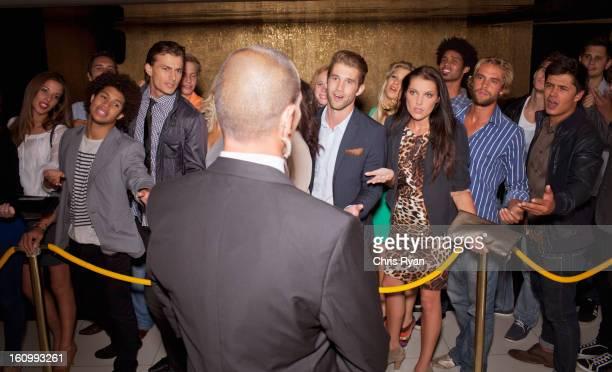 Menschenmenge Gestikulieren, Türsteher hinter dem Seil vor night club