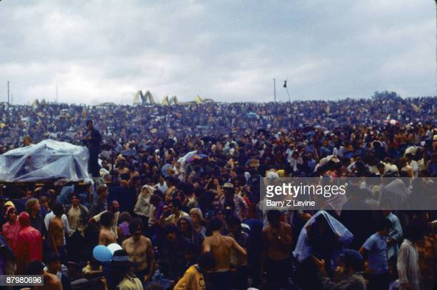 A crowd gets drenched in the rain while others take shelter under plastic tarps at the Woodstock Music and Arts Fair in Bethel New York August 15 17...