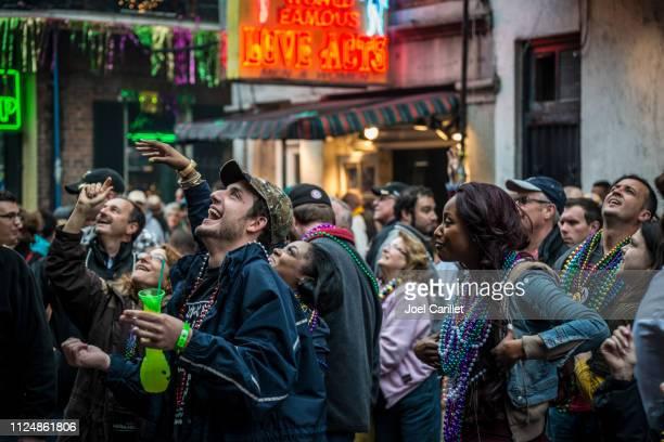 crowd having fun at mardi gras in new orleans - mardi gras fun in new orleans stock photos and pictures
