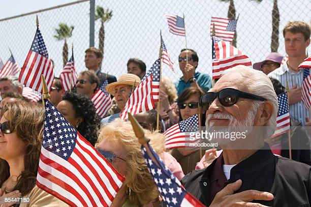 crowd holding american flags - political rally stock pictures, royalty-free photos & images