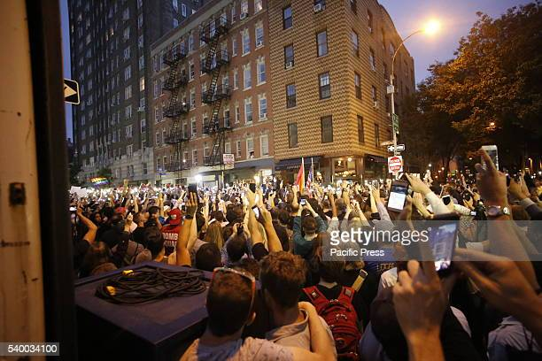 Crowd holding electronic candles aloft fill Christopher Street in NYC's West Village in memory of the victims of the Pulse massacre NY governor...