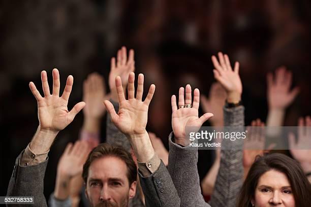 crowd holding up hands in the air - alzar la mano fotografías e imágenes de stock