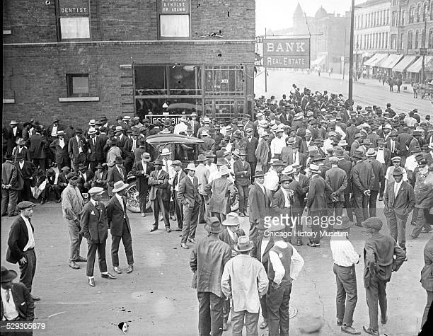 Crowd in front of a storefront with the sign Bank Real Estate during the 1919 Chicago Race Riots