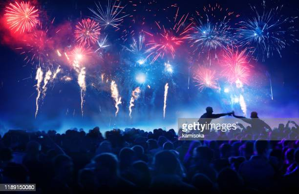 crowd in front of vibrant firework display - fireworks stock pictures, royalty-free photos & images