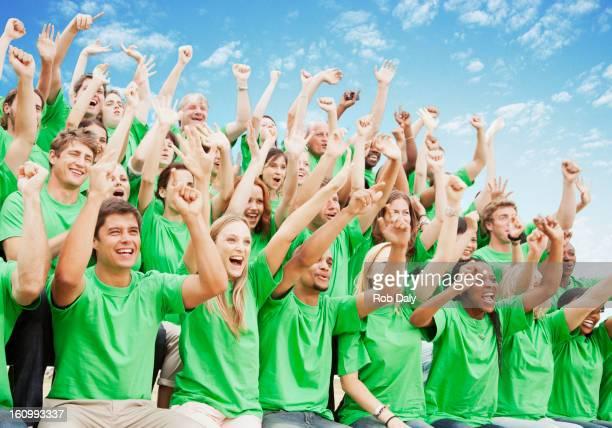 Multitud en verde camisetas aclamando con alzar los brazos