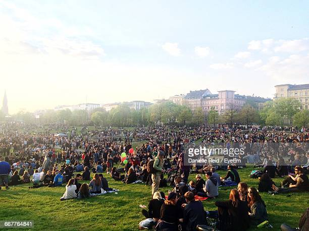 crowd in park against sky - parkanlage stock-fotos und bilder