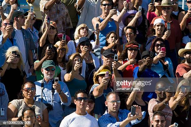 Crowd in stadium watching car racing, photographing with mobile phones (full frame)