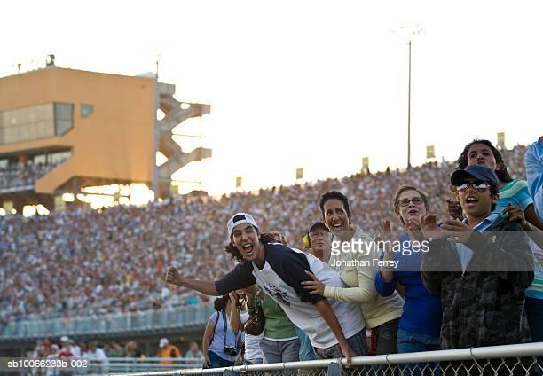 Crowd in stadium watching stock car racing, cheering