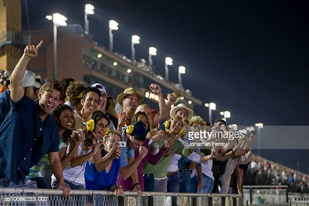Crowd in stadium watching stock car racing, leaning on railings, cheering
