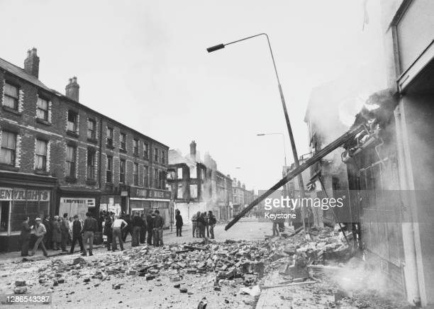 Crowd in the street stand in a brick-strewn road, beside a damaged shop, smoke pouring from the damaged facade, and a leaning lamppost in the Toxeth...