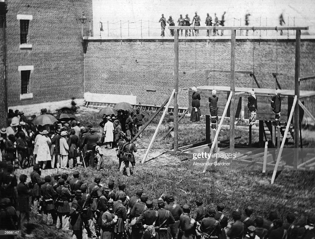 A crowd in the yard of Washington DC's Old Penitentiary, watching the hanging of Mrs Surratt and John Wilkes Booth's conspirators in the plot to kill President Lincoln. The conspirators were Mrs. Surratt, Lewis Payne, David Herold, and George Atzerodt.