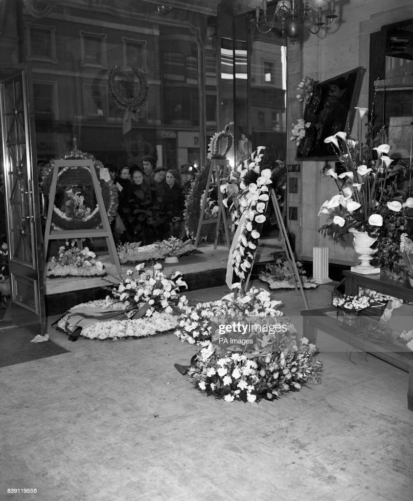 Royalty death of king george vi london pictures getty images a crowd in victoria street london gaze through a window at wreaths prepared for the izmirmasajfo Images