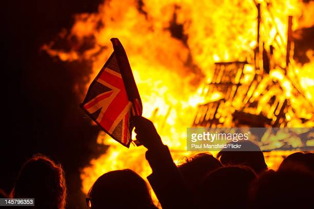 A crowd is silhouetted against the flames after the lighting of the Beacon at Rottingdean June 4 2012 to celebrate the Diamond Jubilee of Queen...