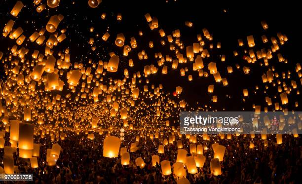 a crowd launching sky lanterns at night in chiang mai, thailand. - yi peng stock pictures, royalty-free photos & images