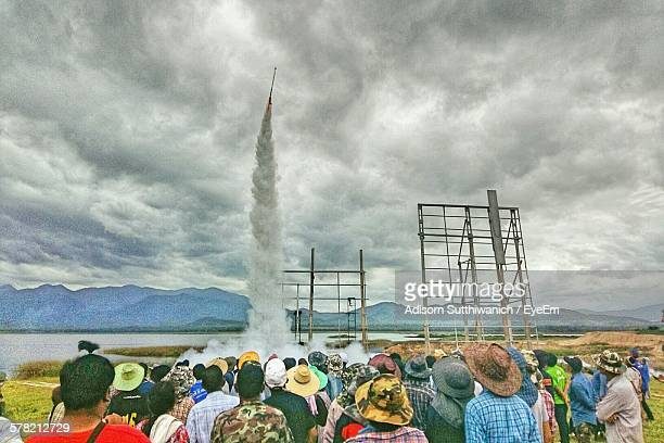 Crowd Looking At Rocket Launch At Riverbank Against Cloudy Sky