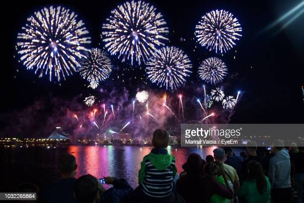 crowd looking firework display at night - firework display stock pictures, royalty-free photos & images