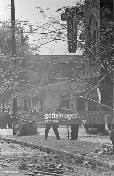 Grim faced crowd of Negroes watch as FBI bomb experts comb rubblestrewn street for clues to 9/15 bombing of the 16th Street Baptist Church Four...