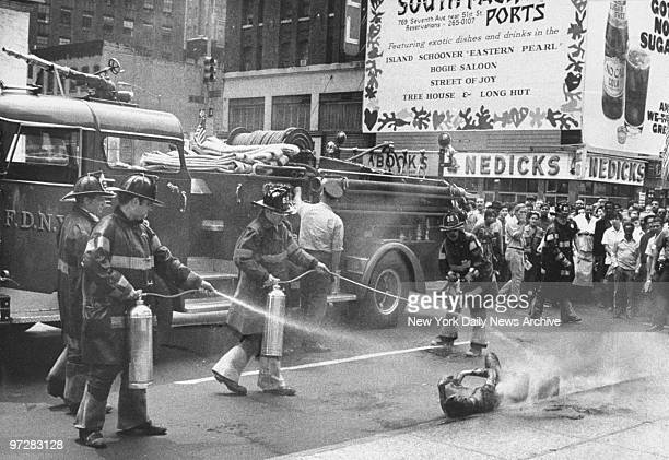 Crowd looks on as firemen attempt to put out flames engulfing a man at Seventh Ave and 42nd Street The man was sitting near the Allied Chemical Tower...