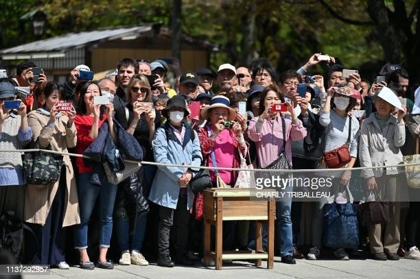 """Crowd looks on as sumo wrestlers take part in a traditional ring-entering ceremony as part of a """"honozumo,"""" a ceremonial sumo exhibition, on the..."""