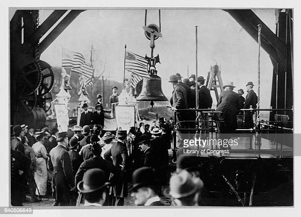 A crowd looks on as the Liberty Bell is transfered from a truck to a train on it way back to Phillidelphia Pennsylvania from the St Louis Exposition...