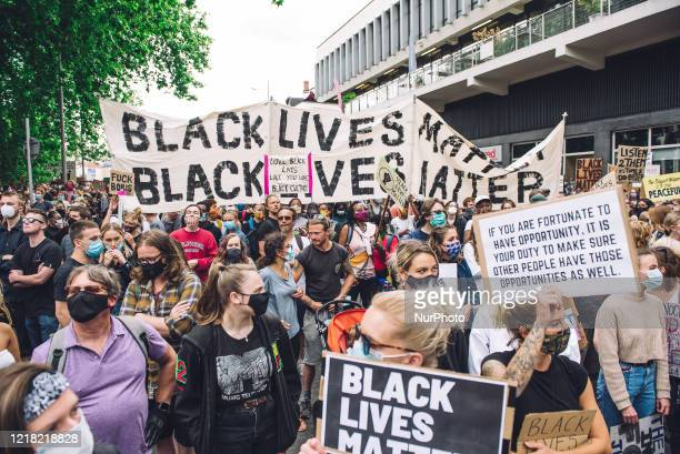 Crowd marches in front of Colston Hall, concert venue dedicated to Edward Colston, a slave trader who lived in the 17th century and played a major...