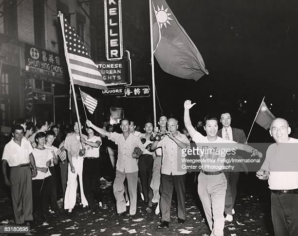 A crowd marches through NY's Chinatown to celebrate the end of World War II VJ Day in Chinatown people are holding American and Chinese flags and...