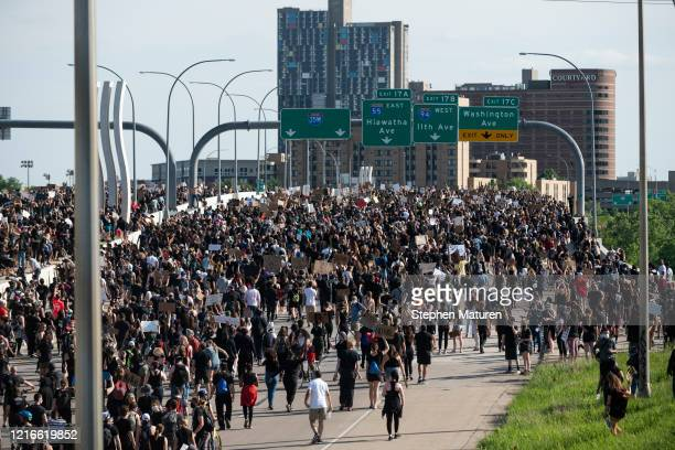 A crowd marches to protest the death of George Floyd on the I35W bridge over the Mississippi River on May 31 2020 in Minneapolis Minnesota The...