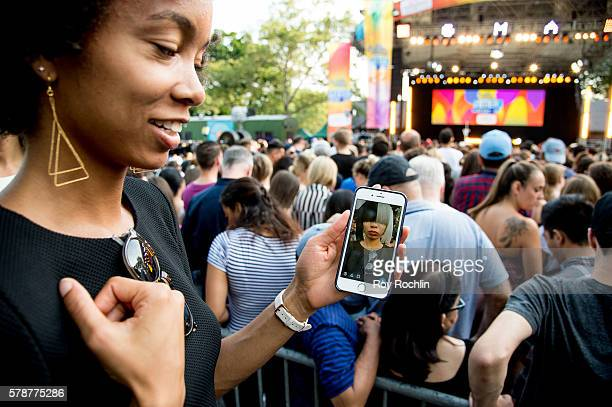 A crowd member uses Snapchat with Sia selfie filter during Sia Performs On Good Morning America on July 22 2016 in New York City