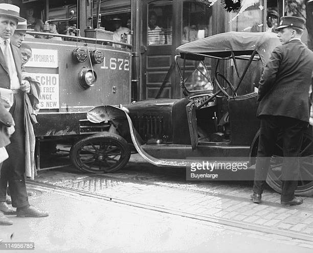 A crowd mills about at the scene of an accident involving an automobile and a trolley early twentieth century The car's left front wheel is pinned...