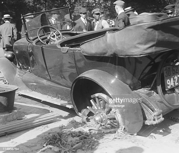 A crowd mills about at the scene of an automobile accident early twentieth century The car shows extensive damage to its rear with a broken wheel and...