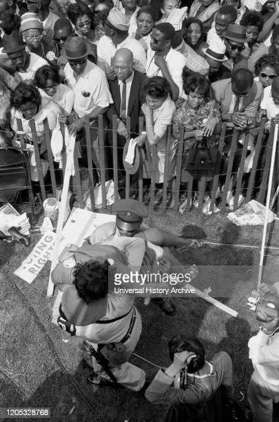 Crowd of African Americans behind a storm fence with police carrying a woman on the other side during March on Washington for Jobs and Freedom,...