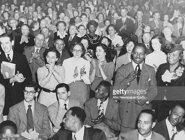 A crowd of AfricanAmerican and white people men and women at a Paul Robeson concert in Philadelphia Philadelphia Pennsylvania October 22 1949