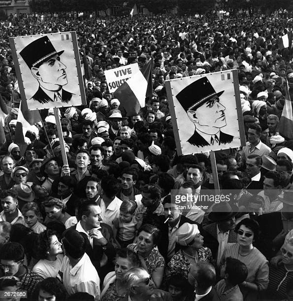 A crowd of Algerian demonstrators outside Government House carrying Charles de Gaulle posters during the Algerian war of independence