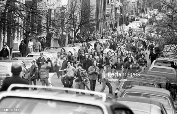 A crowd of antibusing demonstrators storm up East Sixth Street in South Boston armed with rocks and clubs on Feb 15 1976 A demonstration erupted into...
