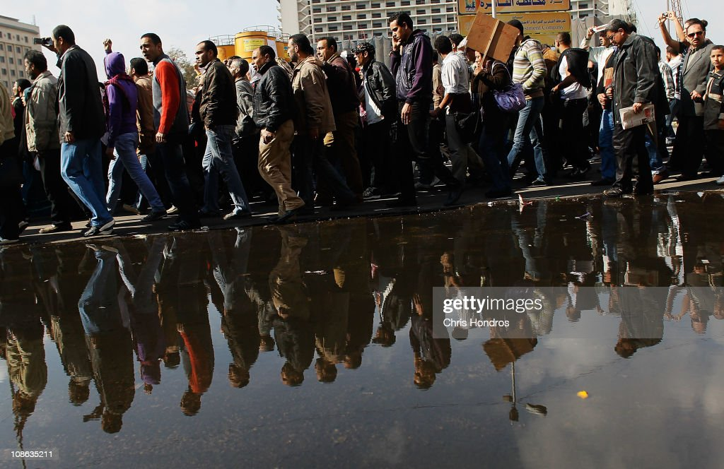 A crowd of anti-government protesters walk past by a large puddle of water from tapped water mains in Tahrir Square on the morning of January 31, 2011 in central Cairo, Egypt. Protests continued into the seventh day as thousands of people marched to demand the resignation of Egyptian President Hosni Mubarak, after 30 years of ruling the country. There is expected to be a ''protest of the millions'' march on Tuesday, whilst the recent unrest is having a knock on effect on the Egyptian economy as tourists, business travellers, and residents are trying to escape the country after a week of anti-government clashes.