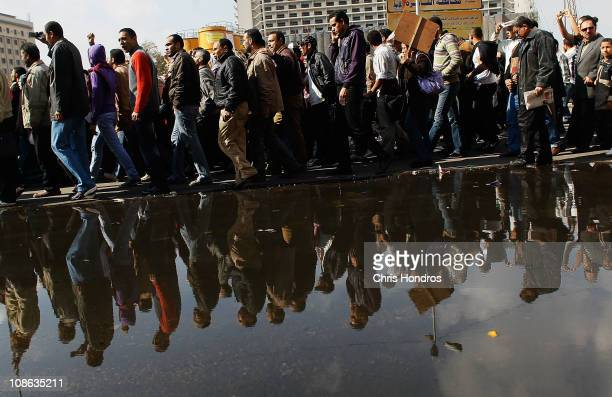 A crowd of antigovernment protesters walk past by a large puddle of water from tapped water mains in Tahrir Square on the morning of January 31 2011...