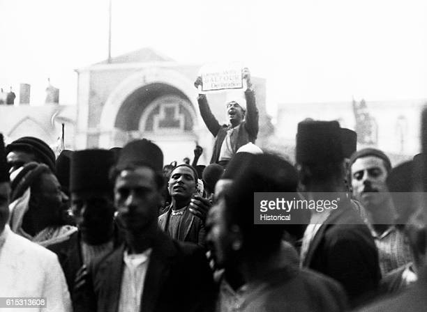 """Crowd of Arab demonstrators protests on the arrival of the Shaw Commission in Jaffa, one demonstrator holding up a sign reading """"Down with the..."""