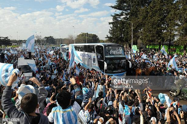 A crowd of Argentinian fans greet their national football team upon their arrival near Ezeiza province of Buenos Aires Argentina after playing...