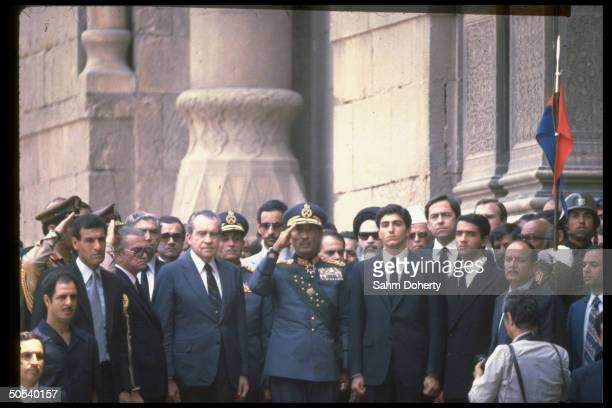 Crowd of attendees including former Pres Richard Nixon Iranian Crown Prince Reza Egyptian Pres Anwar Sadat as he salutes unseen coffin of Shah of...