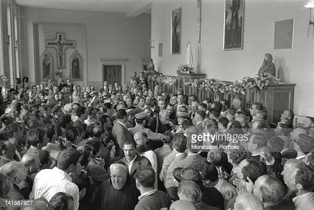 A crowd of believers surrounding Padre Pio of Pietralcina protected by the policemen in the church of Santa Maria delle Grazie San Giovanni Rotondo...