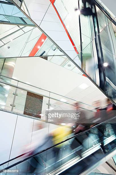 Crowd of Blurred People on Escalator in Modern Glass Interior