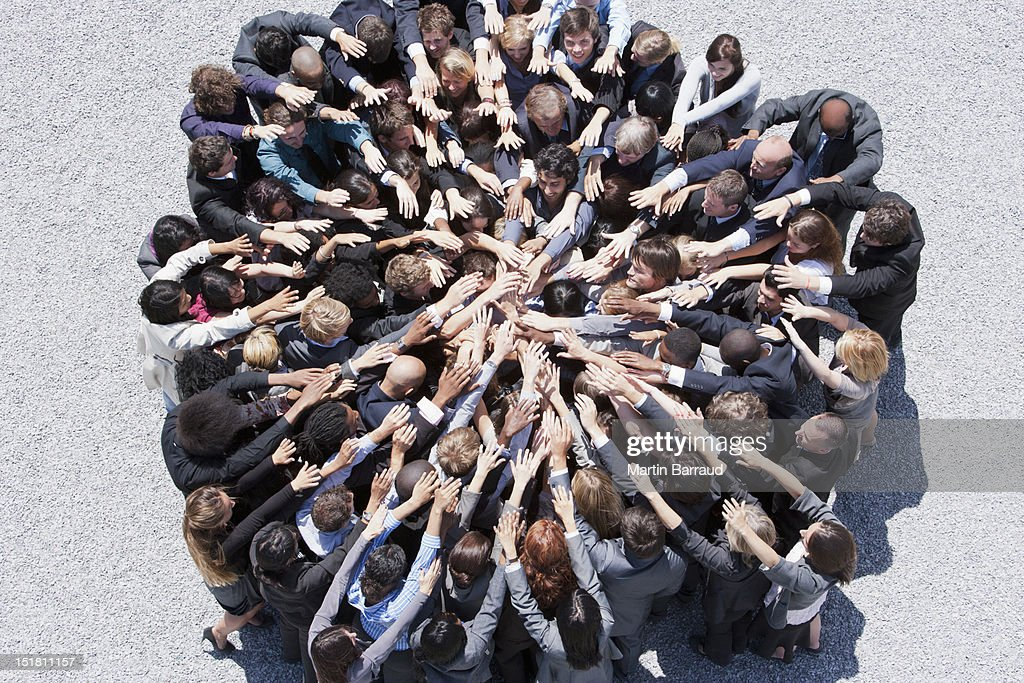 Crowd of business people forming huddle with extended arms : Stock Photo